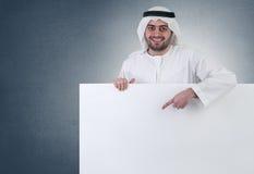 Homem de negócio árabe que aponta em um sinal em branco Foto de Stock Royalty Free