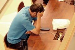 Homem de negócio de Ásia que usa o smartphone e forçado de seu trabalho Conceito da depressão e da ansiedade imagens de stock royalty free