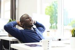 Homem de negócio afro-americano relaxado que senta-se em sua mesa que olha no ar imagem de stock