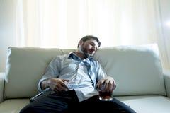 Homem de negócio alcoólico no sono fraco azul do laço bebido com a garrafa de uísque no sofá fotos de stock