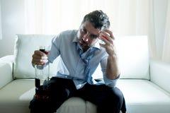 Homem de negócio alcoólico que veste o laço fraco azul bebido com a garrafa de uísque no sofá foto de stock