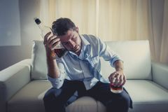 Homem de negócio alcoólico que veste o laço fraco azul bebido com a garrafa de uísque no sofá imagem de stock royalty free