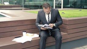 Homem de negócio ansioso que procura algo em um caderno que senta-se fora video estoque