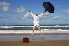 Homem de negócio aposentado que salta com felicidade em uma praia tropical, conceito da liberdade da aposentadoria imagens de stock royalty free