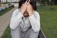 Homem de negócio asiático cansado e furado que senta-se no banco e que sente frustrado imagens de stock