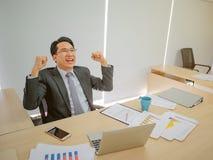 Homem de negócio asiático muito feliz que senta-se em sua mesa imagem de stock royalty free