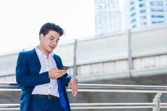 Homem de negócio asiático que fala lendo seu telefone esperto fotografia de stock