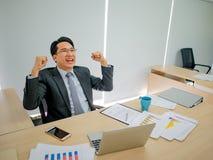 Homem de negócio asiático que senta muito feliz porque seu mercado de valores de ação g fotografia de stock royalty free