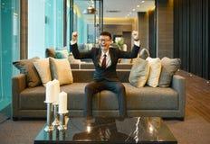 Homem de negócio asiático que sorri no sofá no condomínio luxuoso imagem de stock royalty free