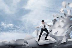 Homem de negócio asiático que surfa na onda dos papéis fotos de stock royalty free
