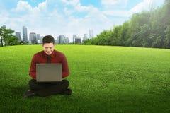 Homem de negócio asiático que trabalha com portátil e que senta-se na grama Imagens de Stock Royalty Free