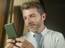 Homem de negócio atrativo e relaxado feliz novo que usa o app em linha texting do telefone celular ou de utilização alegre de sor foto de stock