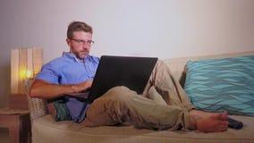 Homem de negócio atrativo feliz novo do empresário que trabalha da casa com o laptop que senta-se no sofá moderno do sofá do apar filme