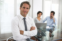 Homem de negócio bem sucedido que está com seu pessoal no fundo em Imagens de Stock Royalty Free