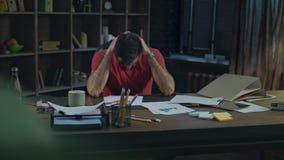 Homem de negócio cansado no escritório acolhedor Homem de negócios novo cansado no trabalho da noite filme