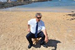Homem de negócio cansado no terno que senta-se na cadeira sobre Imagens de Stock Royalty Free