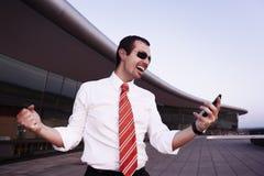 Homem de negócio Cheering com telefone móvel. fotografia de stock royalty free