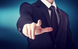 Homem de negócio com apontar a algo ou o toque de um tela táctil Foto de Stock
