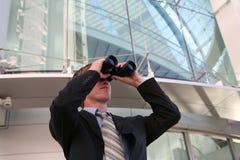 Homem de negócio com binóculos Foto de Stock Royalty Free