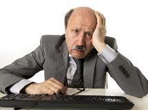 Homem de negócio com cabeça calva em seu funcionamento 60s forçado e frustrado em parecer cansado da mesa do portátil do computad Foto de Stock Royalty Free
