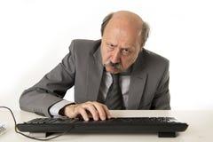 Homem de negócio com cabeça calva em seu funcionamento 60s forçado e frustrado em parecer cansado da mesa do portátil do computad Imagem de Stock Royalty Free