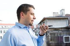 Homem de negócio com camisa azul usando o reconhecimento de voz no telefone esperto no balcão fotografia de stock royalty free