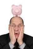 Homem de negócio com o banco Piggy na cabeça e nas mãos na face Foto de Stock