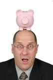 Homem de negócio com o banco Piggy na cabeça e sua boca aberta Imagem de Stock Royalty Free