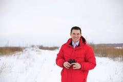 Homem de negócio com o binocular no campo do inverno Fotografia de Stock Royalty Free
