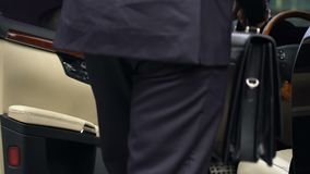 Homem de negócio com a pasta que obtém no carro preto caro, motorista rico video estoque