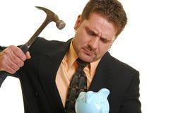 Homem de negócio com um martelo e um banco piggy Fotografia de Stock