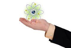 Homem de negócio com uma mão aberta e um símbolo atômico Fotos de Stock Royalty Free