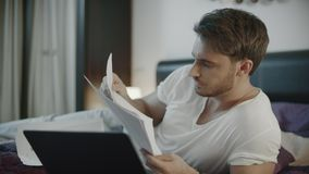 Homem de negócio concentrado que trabalha com o local de trabalho dos papéis em casa na noite video estoque