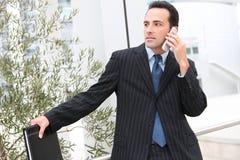 Homem de negócio considerável no escritório no telefone fotos de stock royalty free