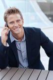 Homem de negócio considerável que usa o telefone de pilha, smil Fotografia de Stock Royalty Free