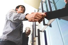 Homem de negócio de sorriso feliz que agita as mãos após um revestimento do negócio Fotografia de Stock