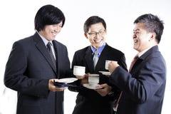 Homem de negócio de três asiáticos com a ruptura de café que tem a conversação foto de stock