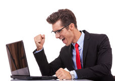 Homem de negócio de vencimento feliz que trabalha em seu portátil foto de stock