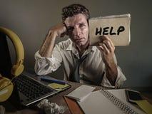 Homem de negócio desarrumado e deprimido novo que mostra o bloco de notas que pede a ajuda desesperada e triste na mesa do laptop fotografia de stock royalty free