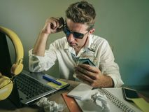 Homem de negócio desarrumado que trabalha na garrafa bebendo da vodca do álcool da mesa de escritório do laptop que olha problema fotos de stock royalty free