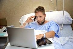 Homem de negócio do viciado em trabalho na sala de hospital que encontra-se no funcionamento doente e ferido da cama com o portát Fotografia de Stock Royalty Free