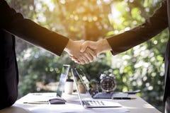 Homem de negócio dois que agita as mãos durante a reunião no escritório com regaço imagens de stock