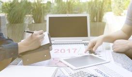 Homem de negócio dois que discute o gráfico financeiro com a tabuleta e o portátil no jardim exterior do parque Fotografia de Stock