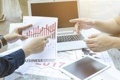 Homem de negócio dois que discute o gráfico financeiro com a tabuleta e o portátil no jardim exterior do parque Imagem de Stock