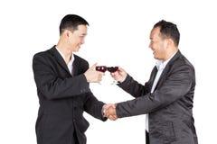 Homem de negócio dois que guarda um vidro do vinho e do aperto de mão Fotos de Stock Royalty Free
