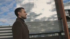 Homem de negócio elegante no revestimento que anda após o fim de vidro do prédio de escritórios acima video estoque
