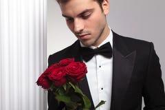 Homem de negócio elegante que olha um ramalhete das rosas vermelhas Imagens de Stock Royalty Free