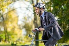 Homem de negócio em uma bicicleta fotos de stock royalty free
