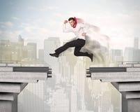 Homem de negócio energético que salta sobre uma ponte com diferença imagens de stock