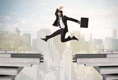 Homem de negócio energético que salta sobre uma ponte com diferença foto de stock royalty free